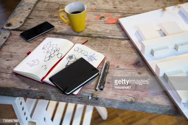 Notebook, smartphone, architectural model and coffee cup in modern informal office