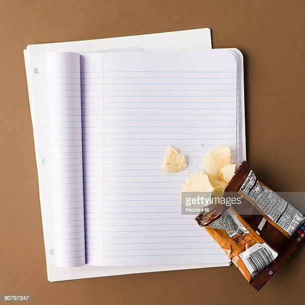 notebook with a bag of chips spilled onto an empty page