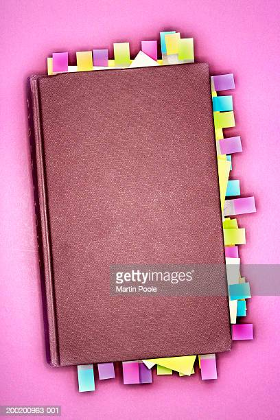 Notebook with sticky notes marking pages, overhead view