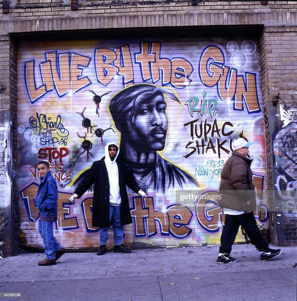Noted graffiti artist Andre 'Baby Man' Charles (b.1968) stands before his tribute mural (since painted over) to rapper Tupac Shakur on on East Houston street in the Lower East Side, 1996. New York.