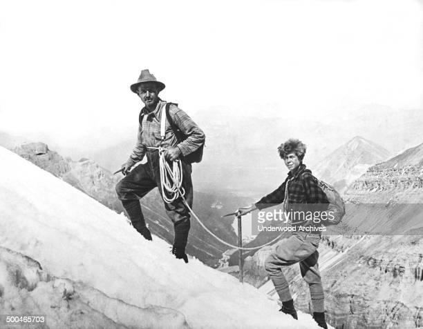 Noted New York climber Georgia Engelhard and Ernest Fuez Swiss guide of the Chateau Lake Louise climbing the snow ridge on Mt Victoria with Lake...