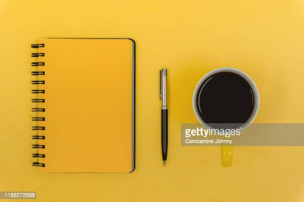 notepad, pen and coffee mug on yellow work desk - to do list stock pictures, royalty-free photos & images