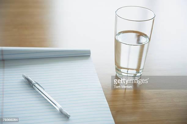 Notizblock und Stift auf dem Bauch liegen und Glas Wasser es