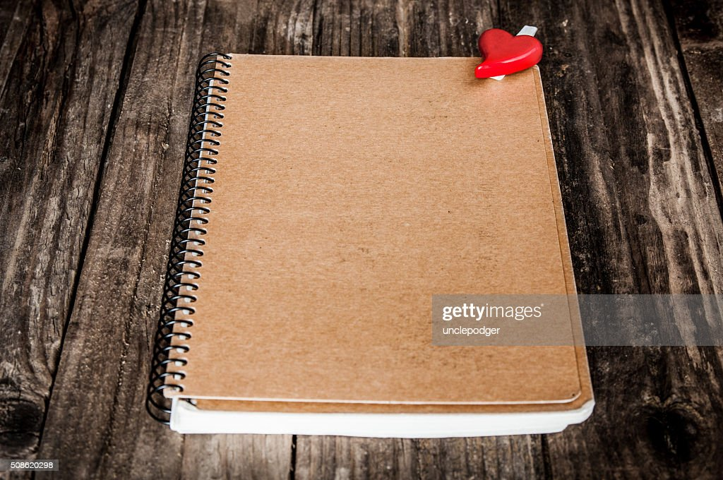 Notepad with red heart on wooden background : Stock Photo