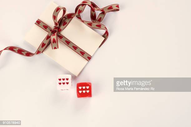 Notepaper with tie bow and two dice with heart shape dice point on white background. Directly above and copy space