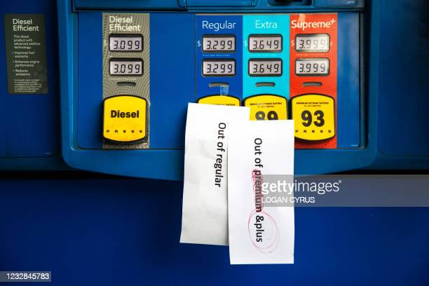 Notes are left on gas pumps to let motorists know the pumps are empty at an Exxon gas station in Charlotte, North Carolina on May 12, 2021. - Fears...