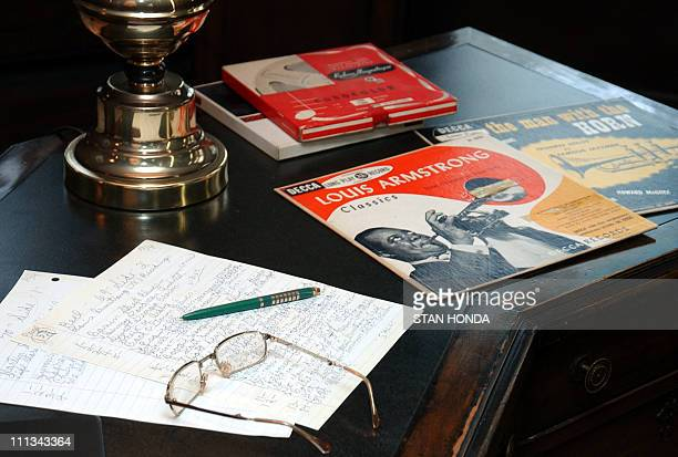 Notes glasses albums and tape boxes sit on the desk in the study of acclaimed jazz musician Louis Armstrong in the Louis Armstrong House 09 October...
