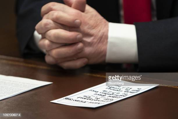 Notes sit next to US President Donald Trump during a meeting about human trafficking on the southern border at the White House in Washington DC US on...