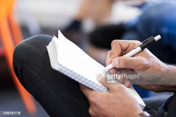 Notetaking on a pice of sheet with a pen during a business meeting