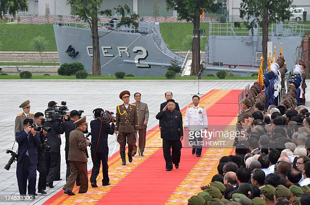 Noth Korean leader Kim JongUn salutes as he walks in front of the USS Pueblo a US navy technical research ship captured by North Korean forces in...