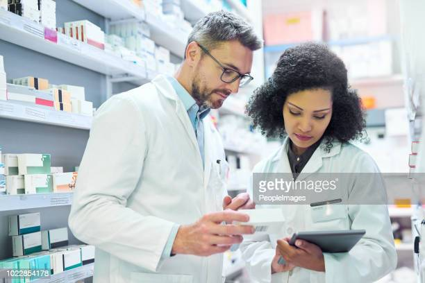 nothing says well run pharmacy like teamwork - pharmacist stock pictures, royalty-free photos & images