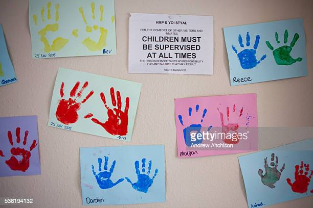 A notice and childrens handprint paintings on the wall of the visitors centre HM Prison Styal is a Closed Category prison for female adults and young...
