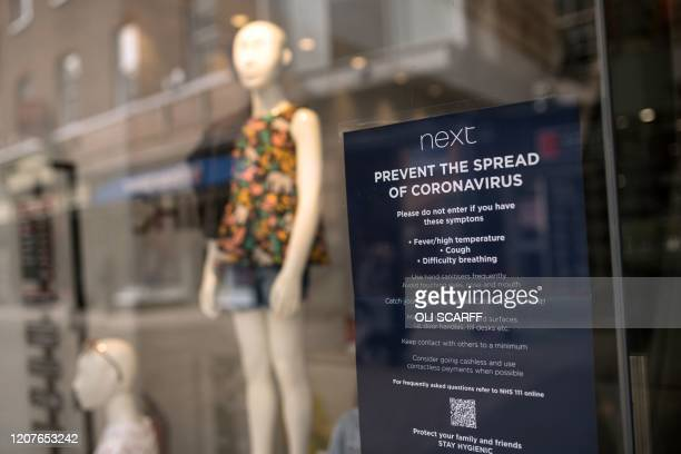 Notice in the window of a branch of a clothing store advises customers on precautions against the novel coronavirus COVID-19 pandemic, in the centre...