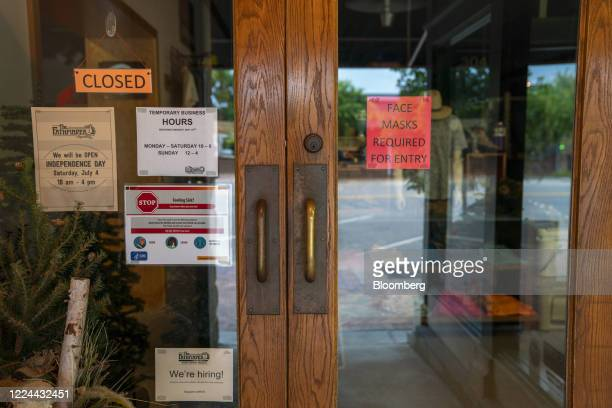 Notice informing customers of face mask requirements is displayed in the door of a closed retail store in Manhattan, Kansas, U.S., on Thursday, July...