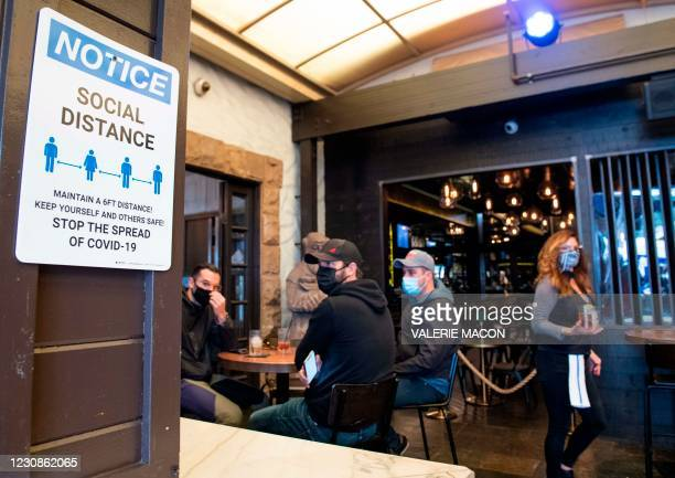 Notice inviting patrons to social distance is seen in the outdoor seating area of The Abbey Food & Bar on January 29, 2021 in West Hollywood,...