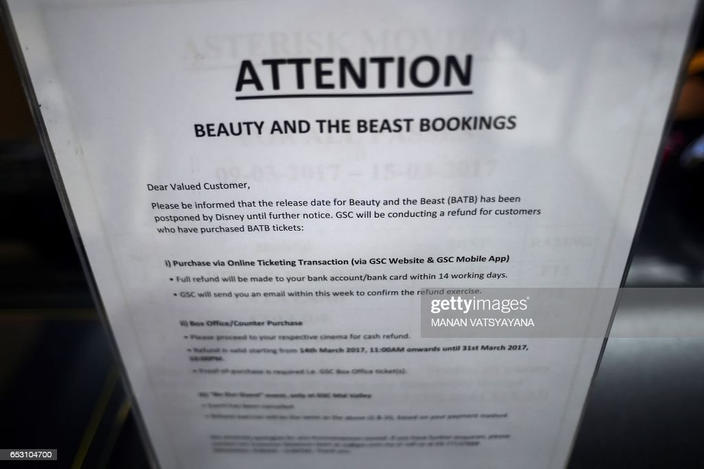 A notice is displayed regarding the release of the film 'Beauty and the Beast' at a Golden Screen Cinemas theatre in Kuala Lumpur on March 14, 2017. Malaysian censors have reportedly cut out a 'gay moment' in the Disney film 'Beauty and the Beast' before agreeing to its release in the Muslim-majority nation. / AFP PHOTO / Manan VATSYAYANA
