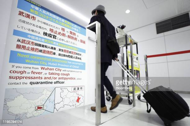 Notice offering guidance to travelers from Wuhan is displayed as a passenger passes through in a quarantine station at Narita Airport in Narita,...