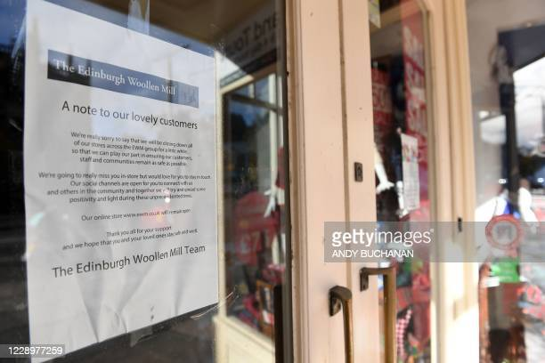 Notice pasted inside the window of a closed branch of The Edinburgh Woollen Mill explains reasons for it's closure, in Edinburgh on October 9, 2020....