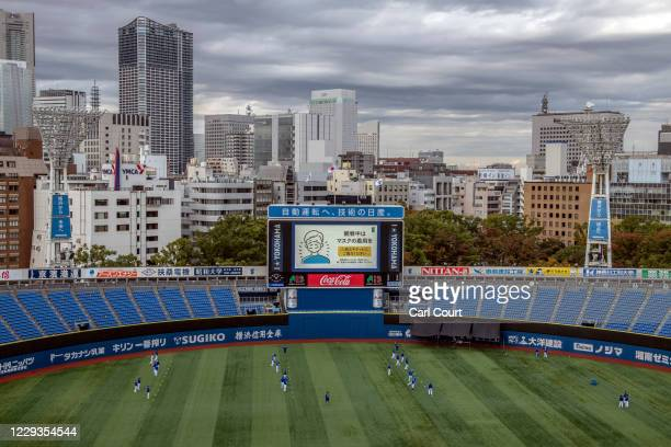 Notice requesting spectators wear a face mask is displayed on a giant screen at Yokohama Stadium as players warm up ahead of a baseball match between...