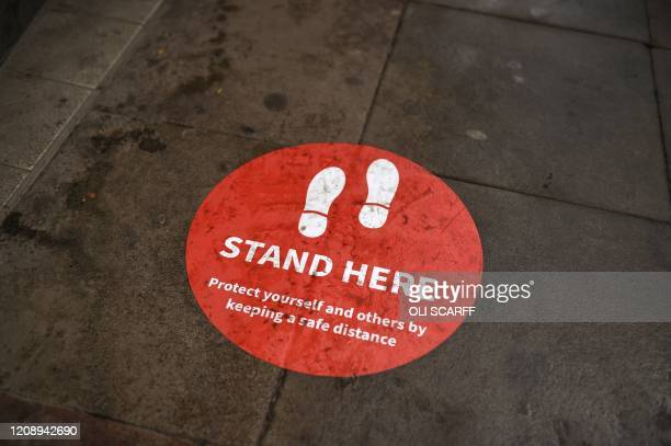 Notice urging social distancing is stuck on the pavement in a shopping area in Manchester on April 2 - Prime Minister Boris Johnson said Britain...