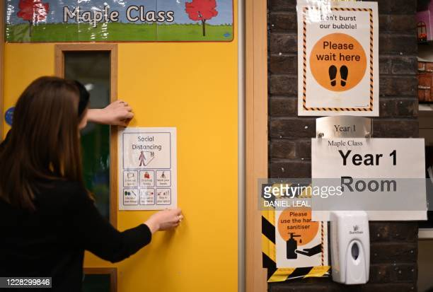 Notices advising hand sanitising and social distancing is seen on a wall as the school is prepared to provide a teaching environment safe from...
