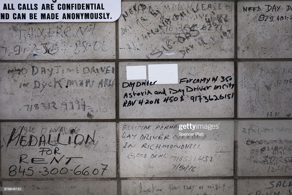 Notices for taxi drivers are written on a wall at a taxi waiting