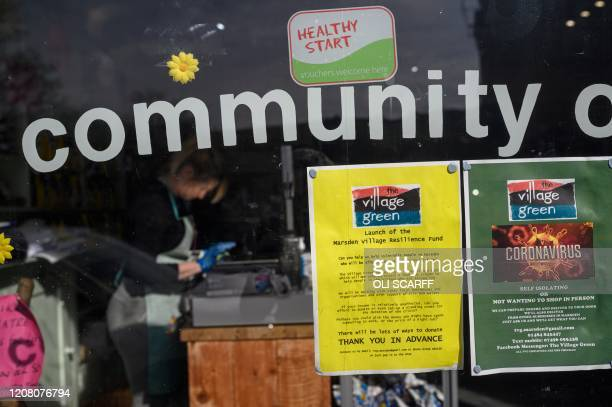 Notices in the window of the community owned grocery shop, The Village Green, offering a free delivery service for local residents self-isolating...