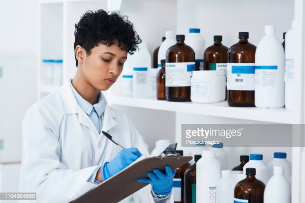 notant tout le stock qu'elle a dans son labo - down blouse photos et images de collection