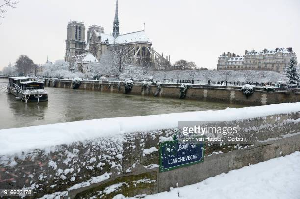 Notre Dame Cathedral is under the snow on Pont l'Archeveque on February 07 2018 in Paris France After a steady snowfall the French capital looked...