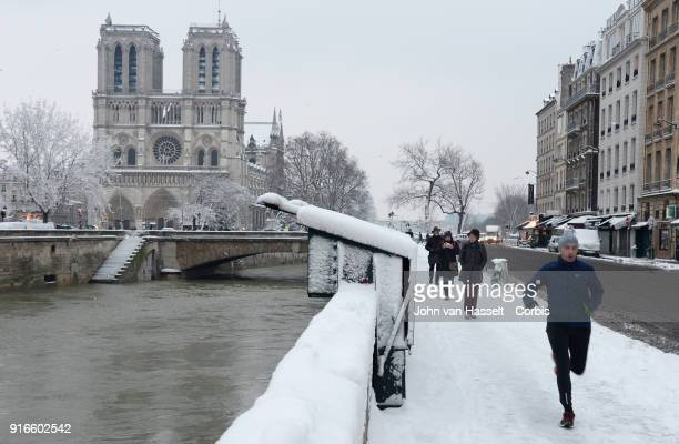 Notre Dame Cathedral under the snow as a jogger runs on February 07 2018 in Paris France After a steady snowfall the French capital looked more...