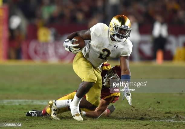 Notre Dame Dexter Williams runs the ball as he drags USC Chase Williams during a college football game between the Notre Dame Fighting Irish and the...