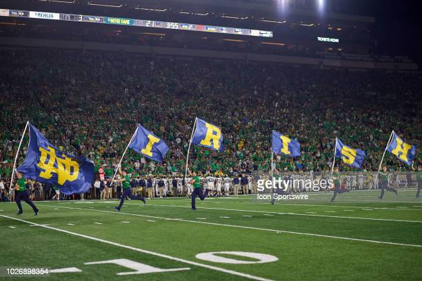 Notre Dame Fighting Irish cheerleaders perform by running down field weaving Notre Dame Fighting Irish flags in game action during the college...