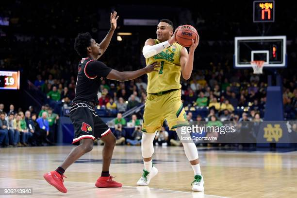 Notre Dame Fighting Irish forward Austin Torres battles with Louisville Cardinals guard Darius Perry during the college basketball game between the...