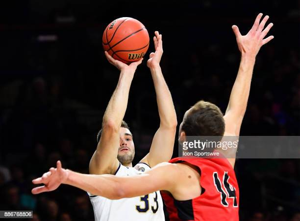 Notre Dame Fighting Irish forward John Mooney shoots over Ball State Cardinals forward Kyle Mallers during the game between the Notre Dame Fighting...