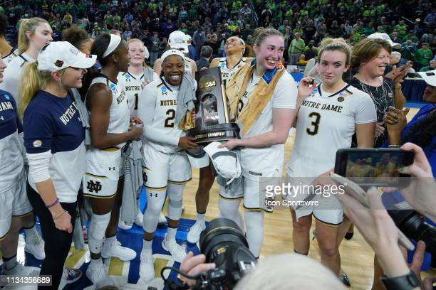 Notre Dame Fighting Irish guard Arike Ogunbowale and Notre Dame Fighting Irish guard Marina Mabrey hold the NCAA Regional Championship trophy and...