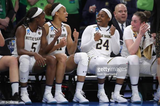 Notre Dame Fighting Irish guard Arike Ogunbowale celebrates with Notre Dame Fighting Irish forward Brianna Turner and teammates on the bench in game...