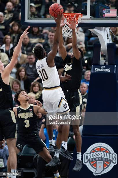 Notre Dame Fighting Irish guard TJ Gibbs shoots over Purdue Boilermakers forward Aaron Wheeler during the Crossroads Classic basketball game between...