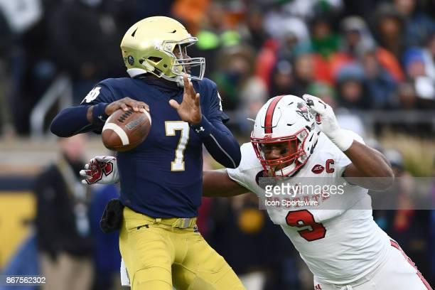 Notre Dame Fighting Irish quarterback Brandon Wimbush battles with North Carolina State Wolfpack defensive end Bradley Chubb during the college...
