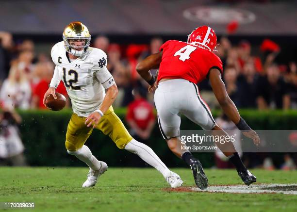Notre Dame Fighting Irish quarterback Ian Book scrambles on fourth down as he is pressured by Georgia Bulldogs linebacker Nolan Smith during the...