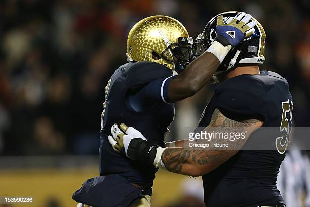 Notre Dame Fighting Irish running back Theo Riddick left celebrates with Notre Dame center Braxston Cave after scoring in the first quarter against...