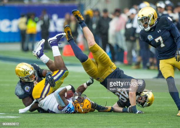 Notre Dame Fighting Irish tight end Cole Kmet tumbles after his block of LSU Tigers running back Darrel Williams during the Citrus Bowl between the...