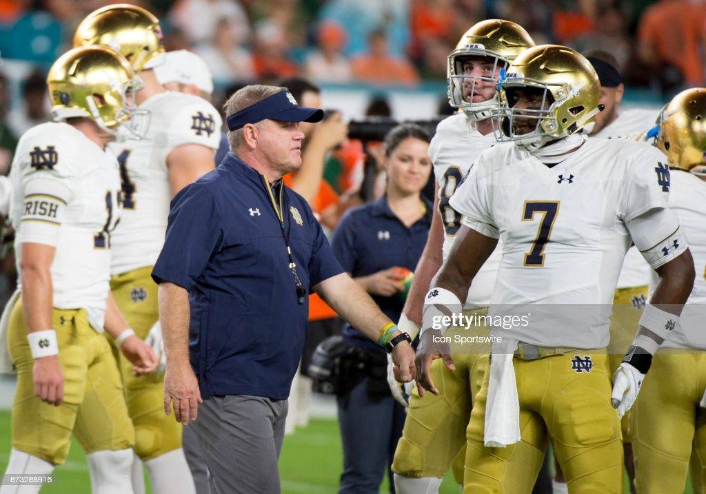 Notre Dame Head Coach Brian Kelly speaks with Notre Dame Quarterback Brandon Wimbush (7) during the college football game between the Notre Dame Fighting Irish and the University of Miami Hurricanes on November 11, 2017 at the Hard Rock Stadium in Miami Gardens, FL.