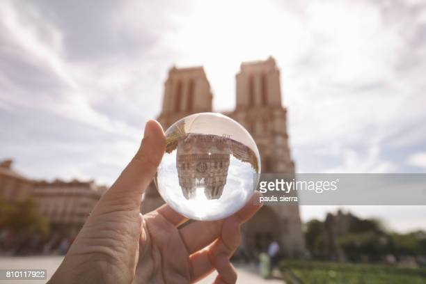 Notre Dame is reflected over a glass ball