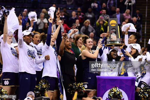 Notre Dame players raise the trophy to celebrate winning the championship against Mississippi State during the championship game of the 2018 NCAA...