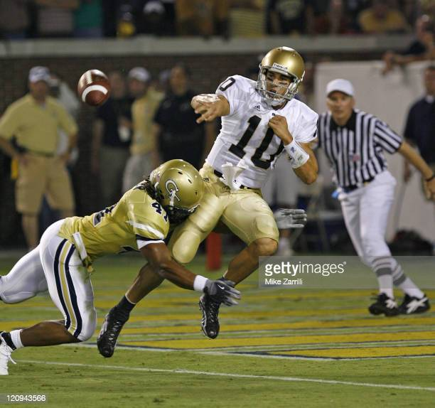 Notre Dame QB Brady Quinn lets go off a pass after being hit by Georgia Tech LB Philip Wheeler during the game at Grant Field at Bobby Dodd Stadium...