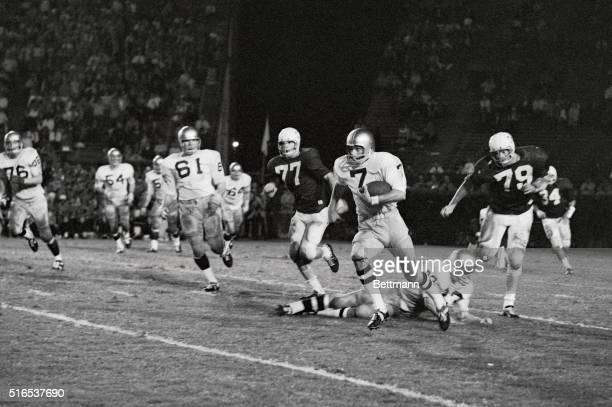 Notre Dame QB Joe Theismann steps over Irish blocker FB Bill Barz as he tries to outrun Tulane DT Mike Walker after Theismann, back to pass, found...