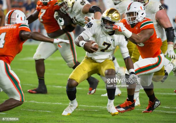 Notre Dame Quarterback Brandon Wimbush runs with the ball as University of Miami Hurricanes Linebacker Darrion Owens grabs his helmet during the...