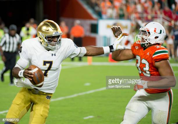Notre Dame Quarterback Brandon Wimbush runs with the ball under pressure from University of Miami Hurricanes Defensive Lineman Trent Harris during...