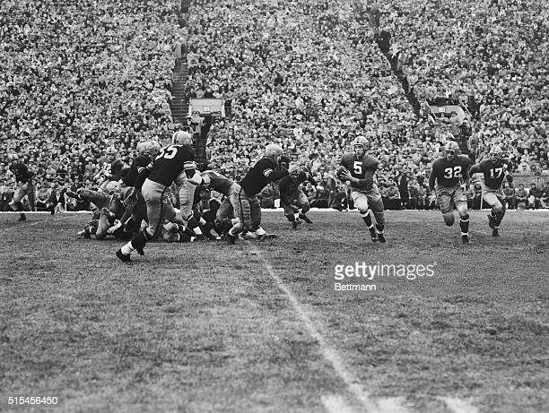 Notre dame Quarterback Paul Hornung starts on a keeper play and is stopped by Fred Harris of Iowa for no gain