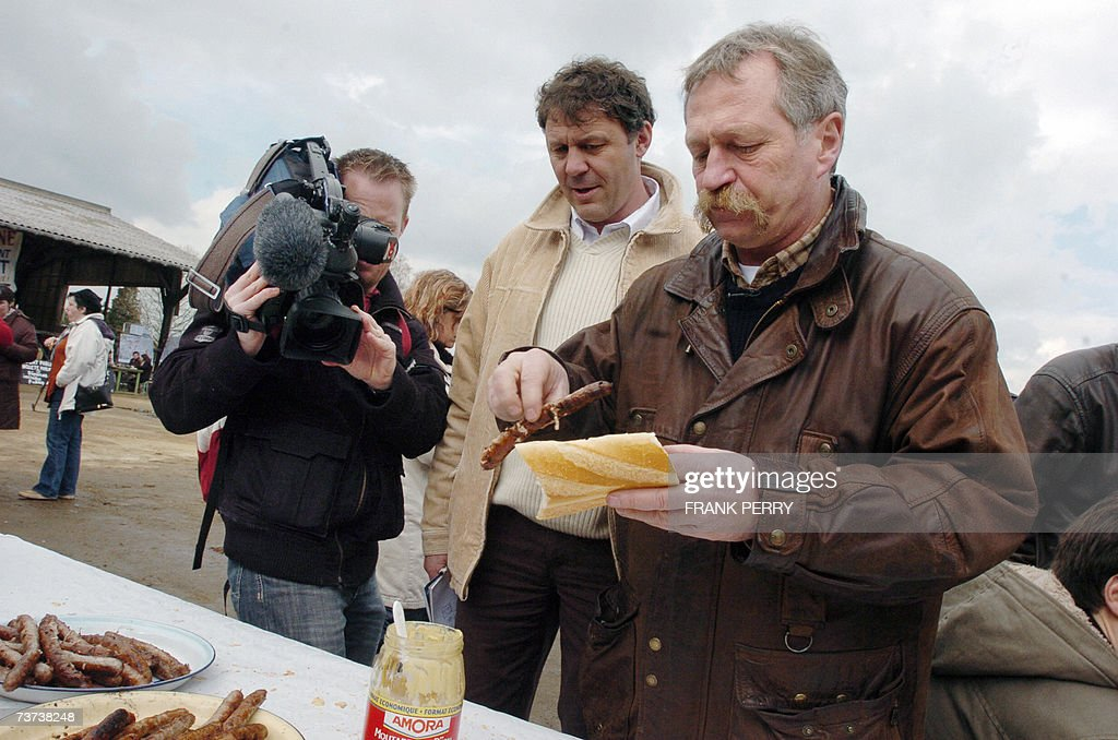 French anti-globalization activist and presidential candidate Jose Bove (R) prepares himself a hot dog during a visit in a farm of Notre-Dame-des-Landes, western France, as part of a visit to support the opponents of an international airport building project in this area.